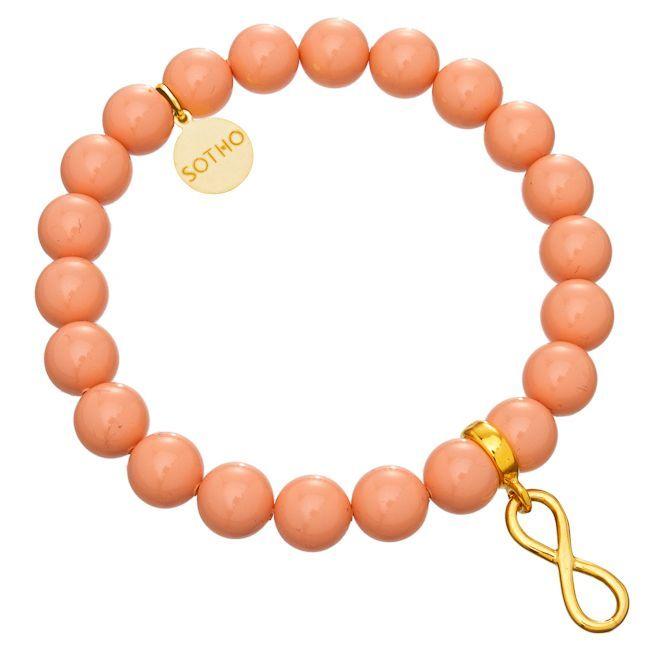 Bransoletka wykonana z łososiowych pereł SWAROVSKI® ELEMENTS  w kolorze Pink Coral, przekładki z symbolem nieskończoności i zawieszki z logo marki. Na zawieszce z logo można grawerować. Wszystkie elementy wykonane ze srebra 925 pokrytego złotem.  http://www.sotho.pl/home/574-lososiowa-bransoletka-nieskoczonosc-infinty-zloto-perly-losos-pink-swarovski-elements-.html
