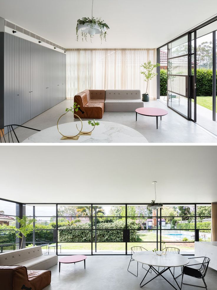 Inside the extension of this renovated house, wrap around black-framed windows make the combined living, dining, and kitchen area extra bright and connect the indoor and outdoor spaces. The grey concrete floor keeps the palette neutral and compliments the darker grey cabinets along the back wall.