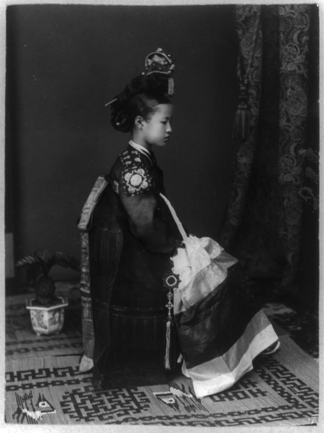 Young palace gisaeng in Seoul, Korea. c. 1910-1920 . This girl is a palace gisaeng, the Korean equivalent of Japan's geisha. The photo is dated to 1910-1920; it's not clear whether it was taken at the very end of the Korean Imperial era, or after the Empire was abolished.  Although technically members of the slave class in society, palace gisaeng probably had a very comfortable life. On the other hand, I would not want to wear that hair pin - imagine the neck strain!