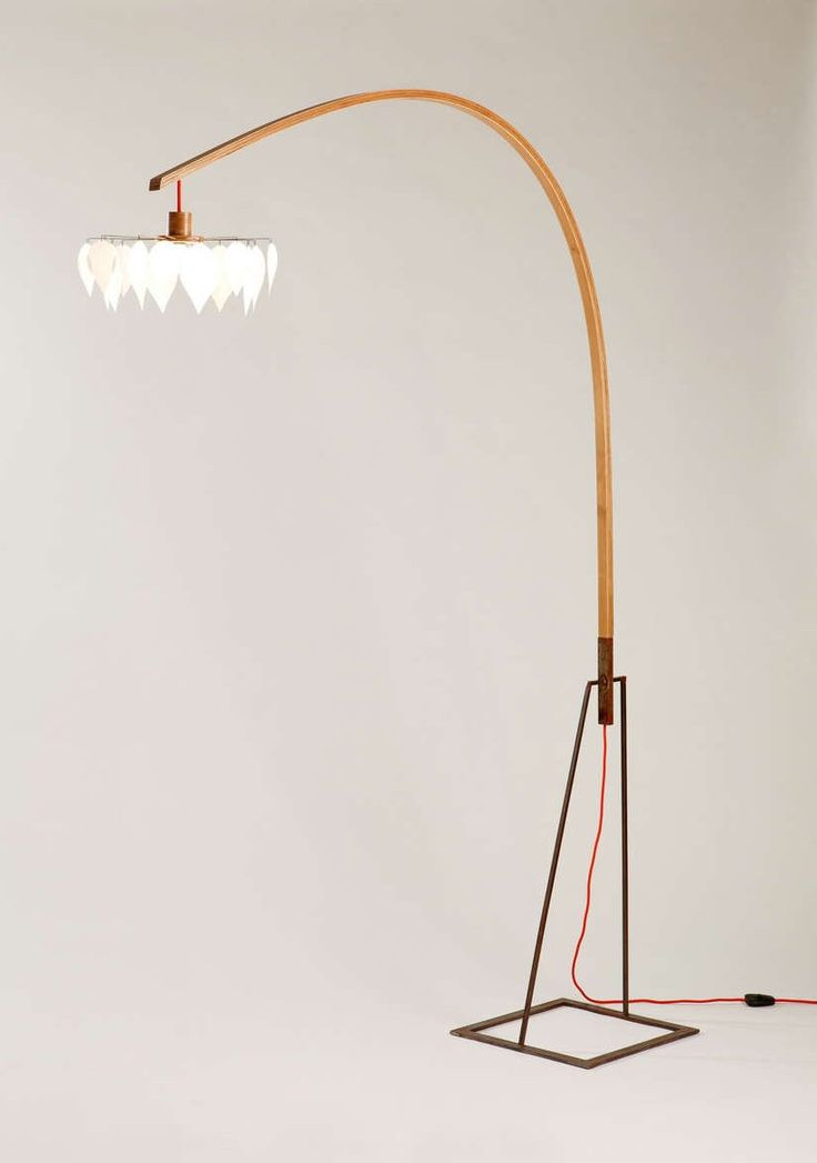 Floor lamp with steel base and wooden arm. The colored fabric cable passes through the curved plywood arm. The light is dimmable.