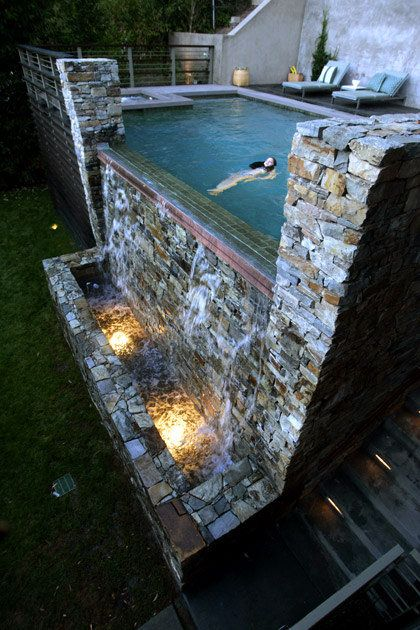 The Freitags' dramatic water wall is made of Oklahoma Chief Cliff stone, and a remote control adjusts the color of the lights in the catch basin as well as the flow of water and its resulting sound.