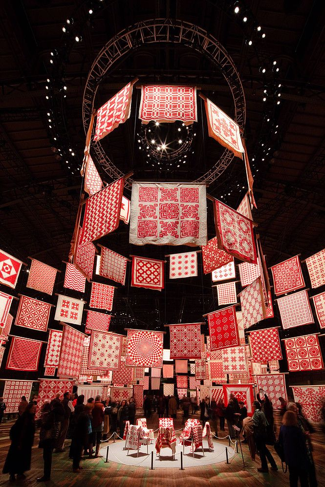 Six 30-foot-high cylinders made entirely of red-and-white quilts surround a 50-foot-high spiral of quilts. Inspired by the geometry of quilting circles, the design responds to the collector's wish to see all the quilts on display at one time, and the curator's desire that they be arranged not by pattern, time period, or region, but in a visually exciting manner. [DISPLAY as Architecture]
