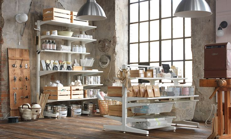 A shop with a white, wall-mounted ALGOT shelf solution, and a free-standing ALGOT solution with mesh baskets.