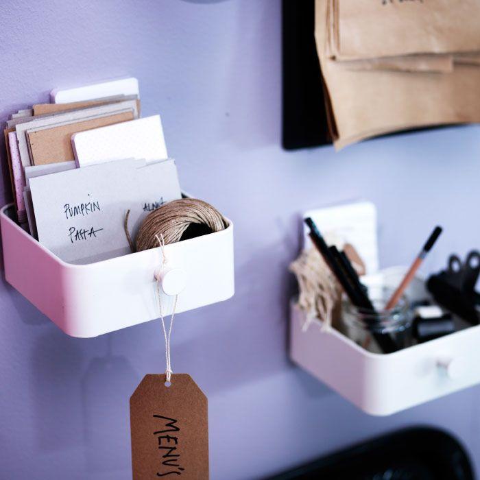 Petite boîte blanche fixée au mur, contenant des cartons et de la ficelle.