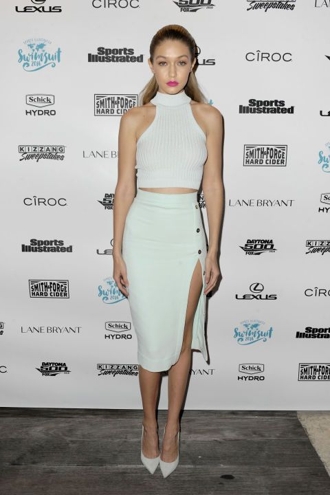 Donning all white, Hadid wore a crop top, high-slit pencil skirt and matching pumps for Sports Illustrated's A Night at Sea VIP Boat Cruise event in Miami.
