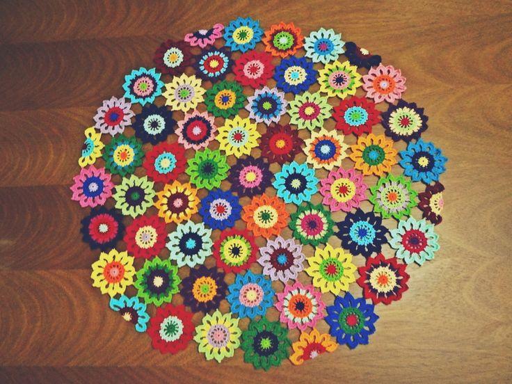 Toalha redonda multicolorida composta por 58 flores com 60 cm diâmetro (aproximadamente). No total, foram utilizadas 21 cores de linhas diferentes (marca Cléa) na confecção das flores.