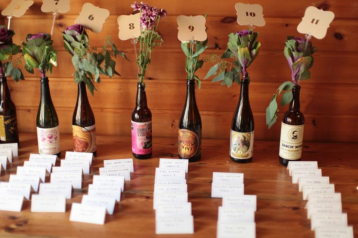 Recycled beer bottles used as table numbers and centerpieces. Photo by Faith Photography