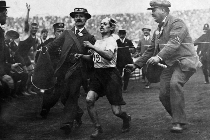 Italian Dorando Pietri is illegally assisted across the finish line and is the apparent winner of the 1908 Olympic marathon in London.  After a protest is filed, Pietri is disqualified and Johnny Hayes of the USA is declared the winner of the gold medal. ~ by Hulton-Deutsch Collection / Corbis
