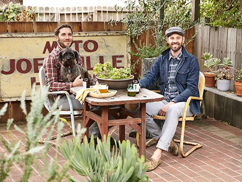 Rod (right) and Andres sit with rescue dog Henri on their brick patio. The furniture came free with the house.
