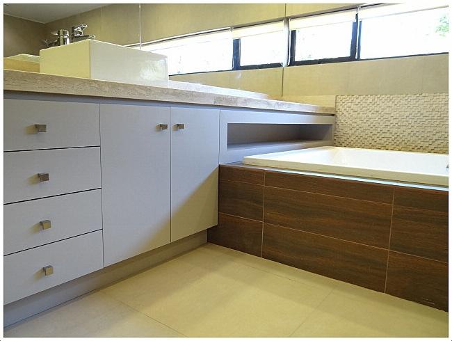 Mueble lavamanos con cubierta de mármol empotrado sobre jacuzzi.  Tiradores de metal satinado.