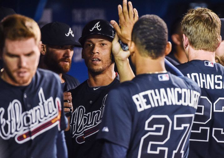 Atlanta Braves' Andrelton Simmons, center, celebrates after scoring on a hit by teammate Eric Young Jr. during second-inning baseball game action in Toronto, Friday, April 17, 2015. (Aaron Vincent Elkaim\The Canadian Press via AP) MANDATORY CREDIT