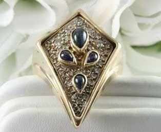 """Visiones fabulosas de estrellas y planetas se revelan en este anillo de propiedad diseñado por Erte. Cuatro cabujones de zafiro azul se elevan sobre un brillante fondo de diamantes en este anillo firmado y numerado diseñado por Erte. Este gran anillo de oro amarillo de 14kt aparece en el libro Ertes Art to Wear en la página 43. El anillo Eternite de Erte """"tiene un aura de misterio que valida el título""""."""