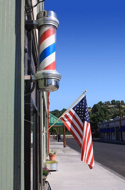 downtown main street USA...beautiful Barber Poles, a thing of the past, I used to love to watch them twirl.