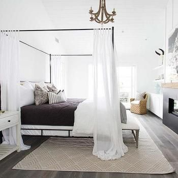Gorgeous master bedroom with hardwood floors, iron canopy bed with headboard and white sheer panels, built in fireplace, white walls and vaulted ceilings | Blackband Design
