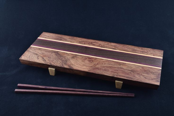 Elegant and simple, this one-of-a-kind Sushi Plate features a gorgeous piece of Figured Bubinga, cut in two and separated by strips of Maple, Purple Heart, and a lovely stick of Walnut. The sliding dovetailed feet are made from Maple as well.  No dyes or stains are used; these are the natural colors of the woods. The dimensions are 5.6 wide by 12 long by 1.4 high.  The chopsticks are included (additional sets can be ordered for $6 each).  As with all of our kitchen and serving products, this…
