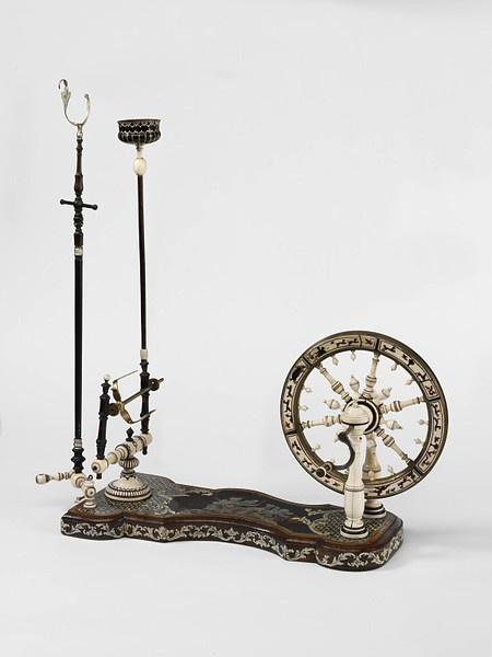 Spinning wheel, Turin, ca. 1740-1750 (made), Piffetti, Pietro, Turned ebony and ivory, the base veneered in tortoiseshell, mother-of-pearl and ivory, with engraved decoration, and with walnut mouldings. Small spinning wheels and winders such as this were made in the 18th century to be used in drawing rooms.Needlework was an important element in the education of young ladies and such equipment allowed them to show off their elegant hands to admirers as they practised their skill. V…