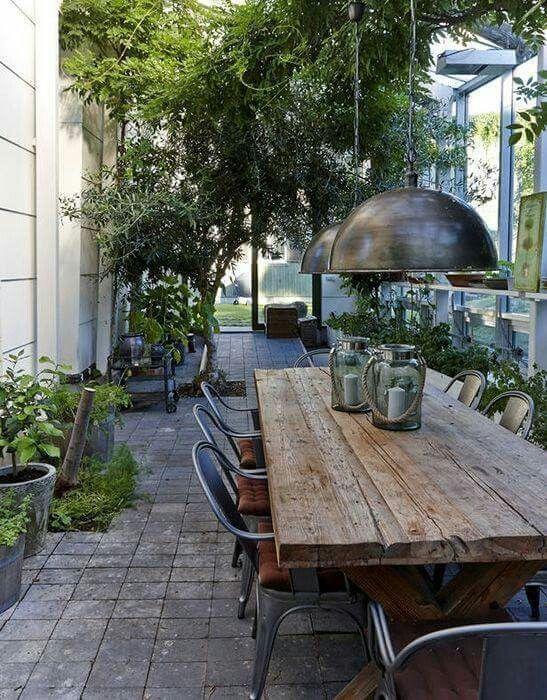 Table en bois brut avec grosses lampes industrielles pour veranda