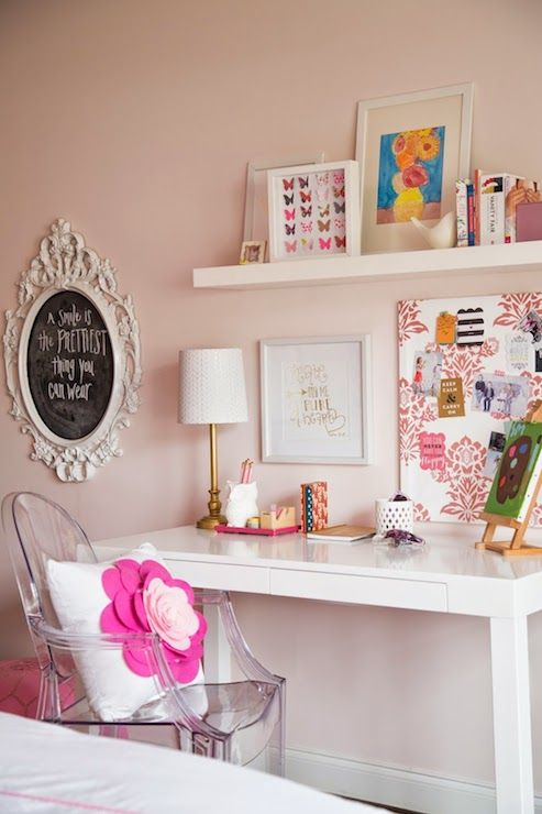 Adorable girl's bedroom features a white baroque chalkboard atop light pink walls painted Benjamin Moore Gentle Butterfly which frame a floating shelf lined with art and trinkets over an Overstock Student Desk and Ghost Chair accented with a pink flower applique pillow.