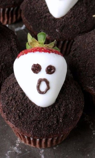 Chocolate Covered Strawberry Ghost Cupcakes - Soft and fluffy chocolate cupcakes topped with chocolate ganache and crushed chocolate cookies get a sweet and spooky spin when you add white chocolate covered strawberry ghosts to the top. Easy Halloween recipe for chefs of all ages. This sweet treat makes a great dessert for Halloween parties at school or in the neighborhood.
