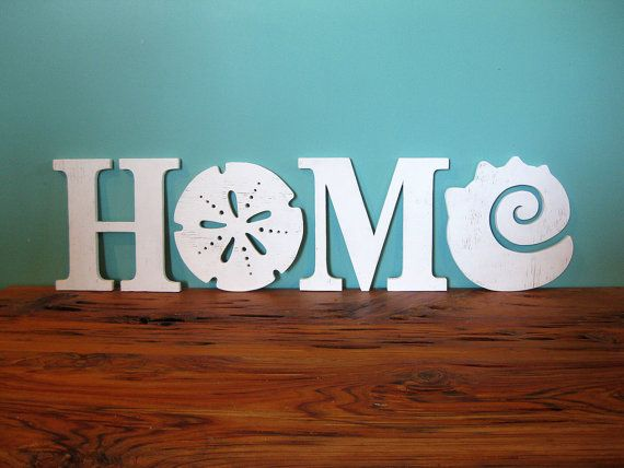 HOME beach word sign with sand dollar and shell design.