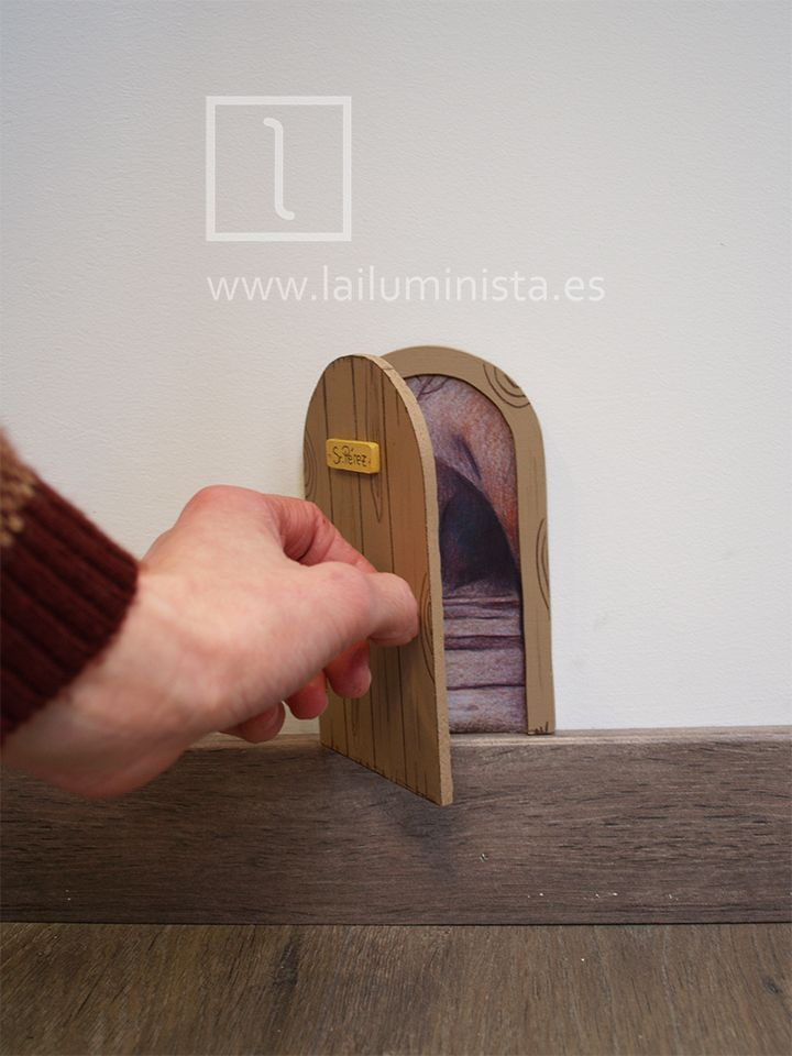 Puerta para el ratoncito Pérez que se abre en color marrón. Está hecha a mano y en su interior se puede ver la ilustración de la cueva a través de la cual viaja el ratoncito Pérez.