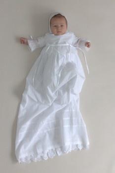 Dåpskjole fra Oli Prik Dåpsklær i bomull i to lag med lange ermer. Blonder, læg og smale satinbånd med små sløyfer. Matchende dåpslue kan kun kjøpes sammen med denne kjole. Lengde 100-105 cm. Str. 62 og 68.