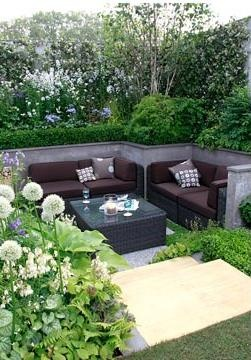 Sunken patio area with white themed border of Alliums, Brunnera and Dicentra in foreground.