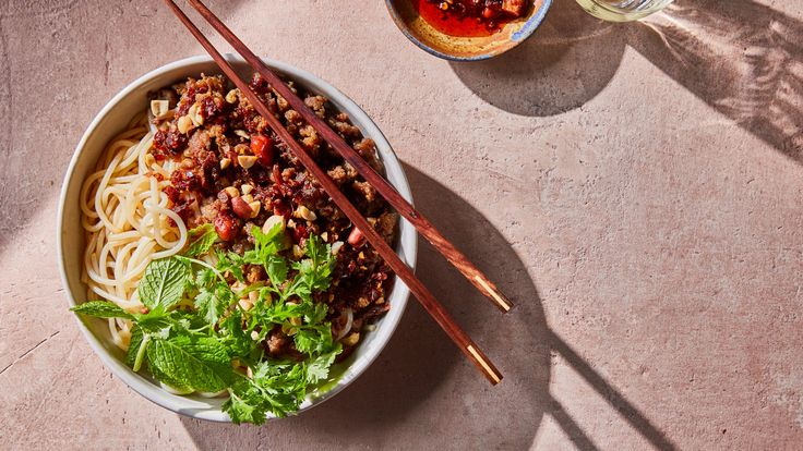 This cold rice-noodle dish, dressed in vinegar and chile oil and topped with spicy pork, herbs and peanuts, has roots in Yunnan, a southwestern Chinese province, where the garnish may vary according to the kitchen and season The dish is quick to put together but can be served at a leisurely pace: Plate it, or set all of the components on the table and let people put together their own bowls the way they like, to their taste The chef Simone Tong, who runs a Yunnan-inspired noodle restaurant…