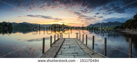 Inviting jetty leading to a dramatic sunset reflected in a perfectly still…