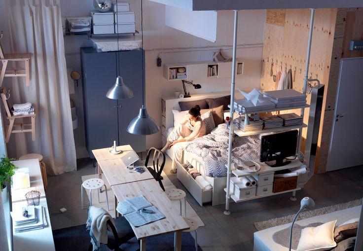 Blick auf eine Frau, die in einer kleinen Wohnung auf ihrem Bett sitzt. Um sie herum ist der Raum geschickt für Aufbewahrung genutzt.