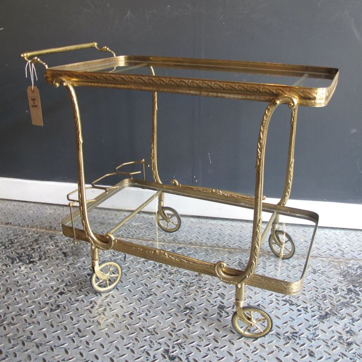 Vintage cocktail drinks trolley which is very Hollywood Regency and bang on trend right now.  With ornate brass frame and two tiered glass shelves it is a beautifully made trolley. It also has a rack section to securely hold your bottles in place whilst you wheel the trolley around.  All the wheels work well and the handle is nice and secure.   Its in great condition the brass is slightly tarnishing in some places but these could be polish...