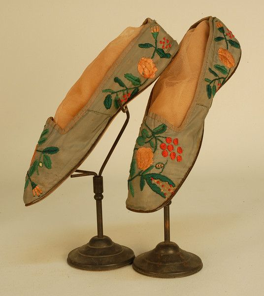 LADY'S FLORAL EMBROIDERED SILK SHOES, LATE 18th C. Grey faille flat straights having square toe, the vamp and quarter decorated with red, apricot and green silk satin stitch flowers, silk bengaline binding, lined in shot silk, linen insole