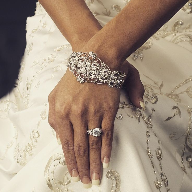 Simply sensational, this bridal bracelet features silver plating and is perfect for your spring, summer, or winter wedding. The bracelet is encrusted with clear rhinestones arranged in a stunning desi