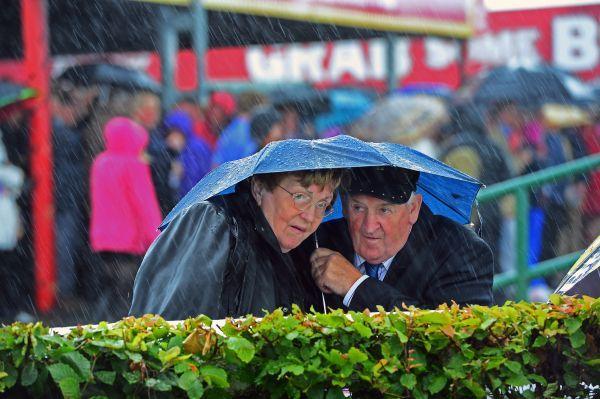 Catégorie Vie quotidienne, 1er prix, Eric Luke (The Irish Times).    Le terrain est mou.    Le terrain est mou, des parieurs se mettent à l'abri d'une averse lors des courses de Galway.