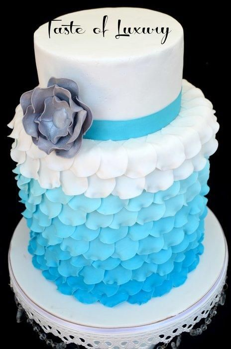 One of my favourites to make, this is a double barrel tier covered in blue ombre ruffled rose petals topped with a single tier in white with a silver sugar flower. Flavours: chocolate mud, cookies & cream mud, fruit cake....