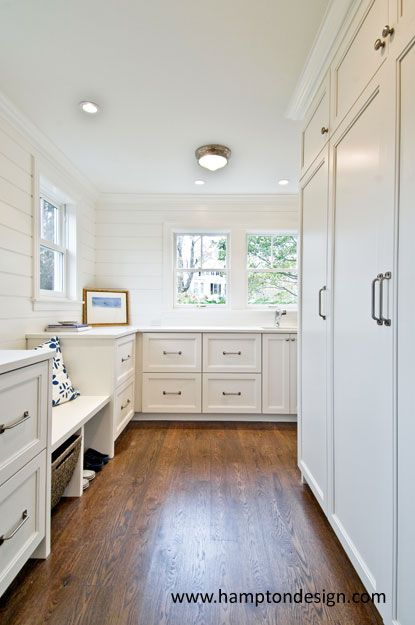 Stunning mudroom with wall to wall white built-in cabinetry and a built-in bench with open storage below.