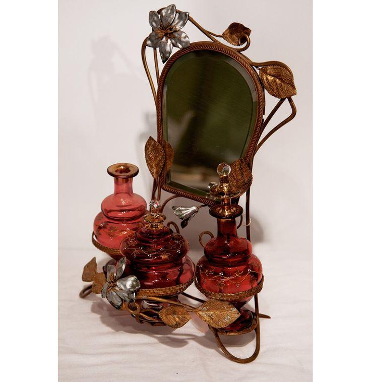 """УКРАШЕНИЕ ДЛЯ ДАМСКОГО ТУАЛЕТНОГО СТОЛИКА """"ЗЕРКАЛО С ФЛАКОНЧИКАМИ"""". Латунь, стекло                                           Европа, XIX век  Набор состоит из небольшого зеркальца, по форме напоминающего подкову, на металлической подставке, и трех флакончиков. Изящная подставка, выполненная в металле, прекрасная интерпретация растительной тематики в декоративно-прикладном искусстве. Н34см. 20 000р."""