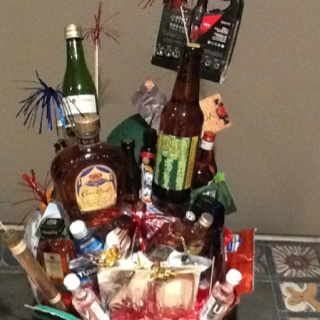 40th birthday basket   My husband got this basket for his birthday from our friends. They used a tool belt for the bottom and filled the pockets with snacks. The other items in the basket are booze, gift cards, tylenol for aches and pains,various snacks, and a large chocolate number 40. Cute idea!
