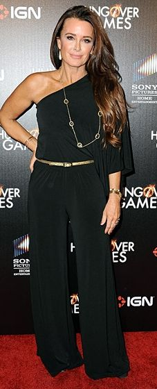 Kyle Richards wears a one-shouldered black jumpsuit with gold belt to The Hungover Games premiere