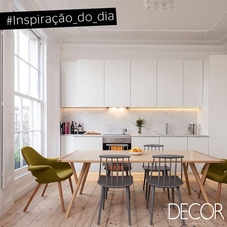 Pouco se usa de luz artificial nesta cozinha, pois a imponente janela joga iluminação natural para o cômodo. Os armários em branco unem-se às paredes de mesma cor, destacando o chão em madeira clara. A mesa e as cadeiras - em verde e cinza - dão cor ao ambiente, o deixando mais moderno e harmonioso.