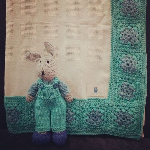 Organic cotton cot blanket in cream with a hand crochet blue and aqua border, with matching hand knitted bunny