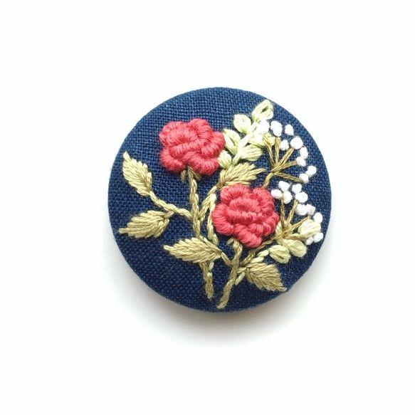 (こちらの作品は、他サイトでも販売中のため万が一注文が重なった場合は、同じ構図で新しく製作したものをお送りいたします。手刺繍ですので、全く同じにはならない場合もございますがあらかじめご了承ください。)バラの花をメインに、草花の刺繍をあしらった作品です。生地はインディゴブルー色の麻素材です。手刺繍のため、同じものは二つとありませんが、同じモチーフでのオーダーは可能です。くるみボタン直径約4cmくるみボタン/金属生地、刺繍糸/麻、綿