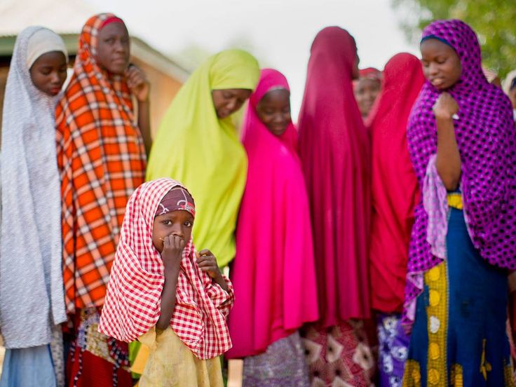 A young Nigerian girl from the Hausa tribe stands next to the line as her mother joins others queuing to validate their voting cards, at a polling station located in an Islamic school in Daura, the home town of opposition candidate Gen. Muhammadu Buhari, in northern Nigeria