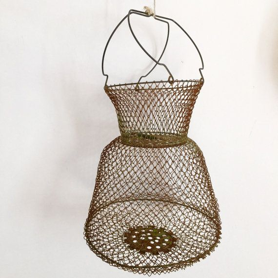 """French Antique Mesh Double Tiered Fishing Basket - Rustic Kitchen Decor   Antique French Collapsible Mesh Fishing Basket or Bourriche with gorgeous rustic Copper-like Patina  This beautiful rustic fishing basket is a traditional french """"Bourriche"""" hand made and used to live catch fish and crustaceans here in France and throughout the Mediteranean. This one has a lovely patina with a tint of turquoise and rusty red giving a special rustic patina. There is a hinged panel in the middle that…"""