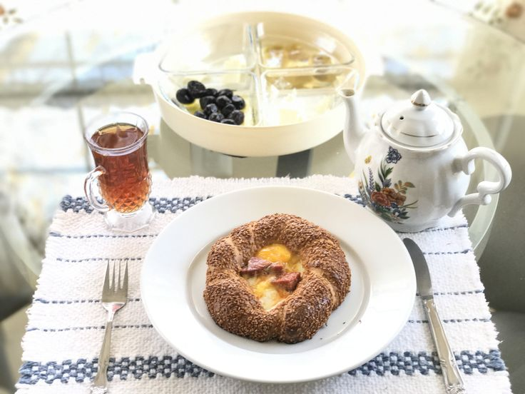 Simple breakfast with simit, sucuk, egg, kaşar, olives, feta cheese, and fig jam and Turkish tea