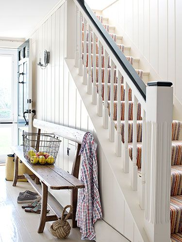 The homeowner acquired this antique bench—a perfect fit for the front hall—from the home's former owners. The walls are painted Monterey White by Benjamin Moore.