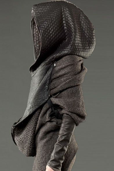 Post-Apocalyptic Fashion.  This appears to be a poncho/carrying bag.   It looks like it was knit and then vinyl bonded somehow.