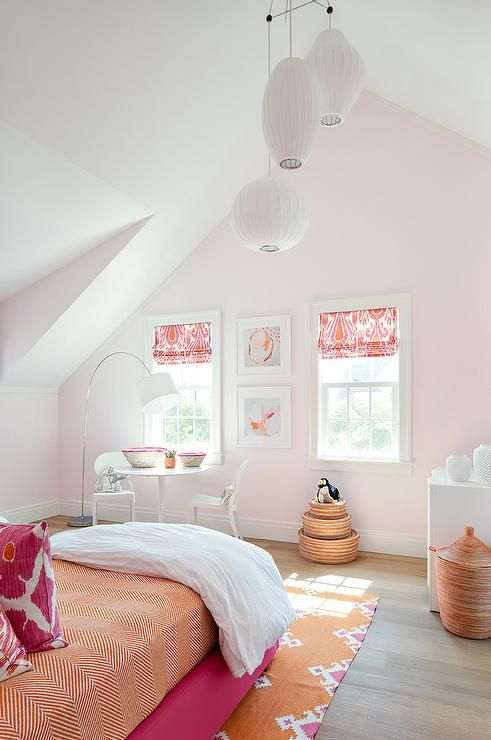 Hot pink and orange girl's bedroom boasts staggered rice paper lanterns illuminating a hot pink upholstered bed dressed in an orange chevron sheet set as well as hot pink ikat pillows placed atop a orange and hot pink ikat rug.
