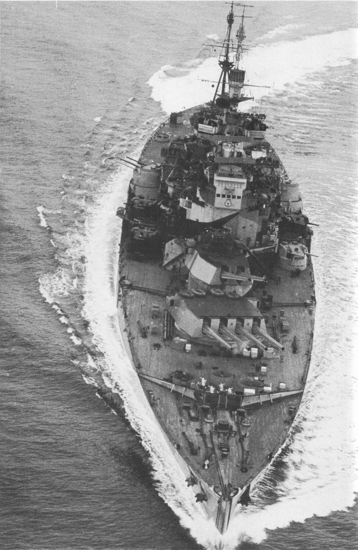 Battleship HMS Howe maneuvers off Okinawa with her main armament assuming firing position aimed at Japanese targets on the island. She was attached to Task Force 113 supporting the US landings.