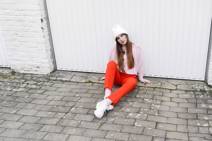 Red costume pants with a bubblegum pink sweater and Puma Blaze sneakers